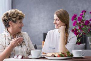 Une auxiliaire de vie à table avec une personne âgée