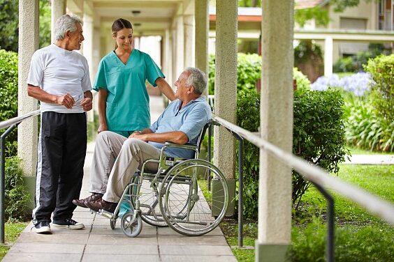 Une personne âgée dans un fauteuil roulant entouré d'une infirmière