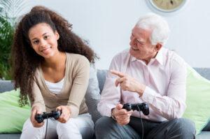 Une personne agée et une jeune entrain de jouer à un jeu vidéo