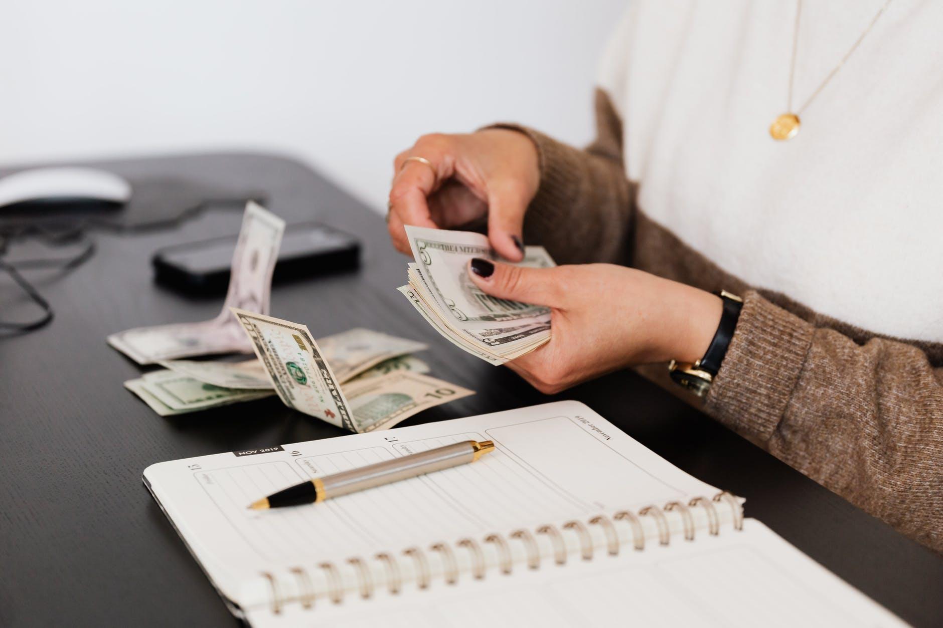 Une femme avec des billets à la main sur un bureau