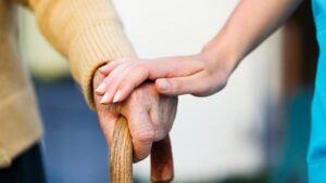 Une infirmière tenant la main à une personne âgée avec une canne