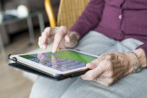 personne âgée malade alzheimer joue jeu de cartes sur tablette tactile